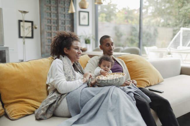 Los padres con la hija bebé viendo la película con palomitas de maíz en el sofá - foto de stock