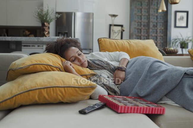Mujer cansada durmiendo en un sofá junto a una caja de bombones - foto de stock