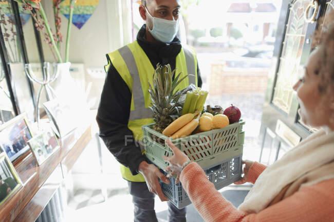 Жінка отримувала доставку продовольства від доставки чоловіка в масці. — стокове фото