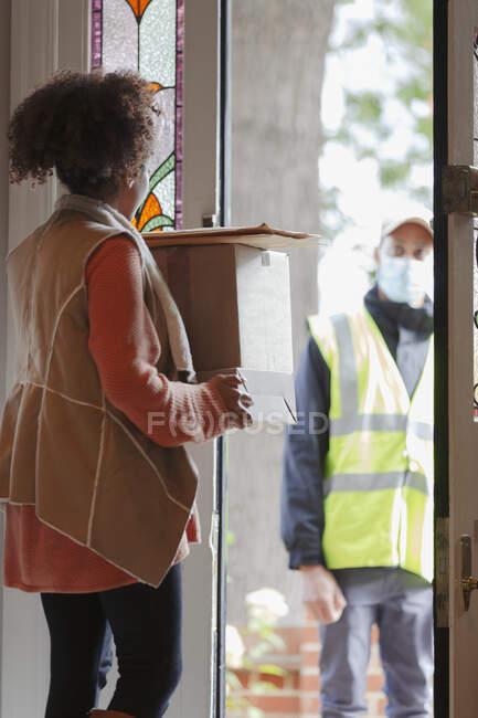 Женщина получает посылки от курьера в маске на двери — стоковое фото
