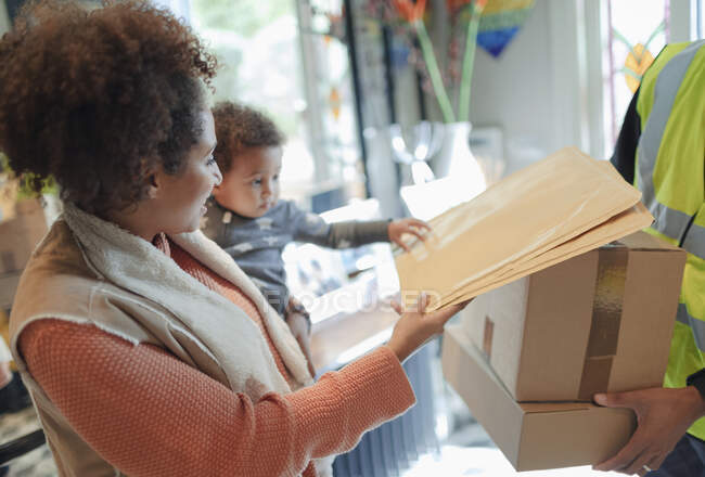 Mother and baby daughter receiving package from delivery person — Stock Photo