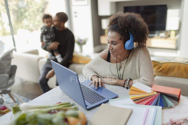 Жінка працює на ноутбуці з чоловіком і донечкою на задньому плані. — стокове фото