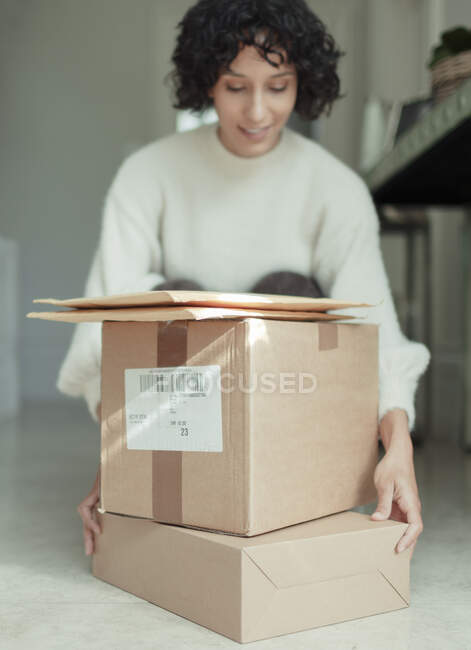 Woman receiving packages stacked on floor — Stock Photo