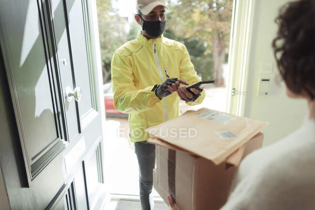 Женщина получает посылки от курьера в маске на входной двери — стоковое фото