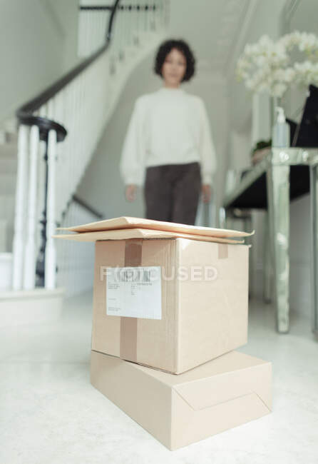 Женщина приближается к стопке коробок для родов на полу в фойе — стоковое фото