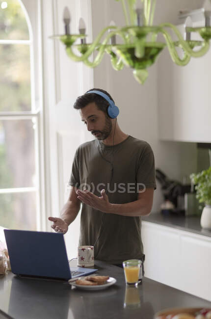 Man in headphones on video call working from home at laptop in kitchen — Stock Photo