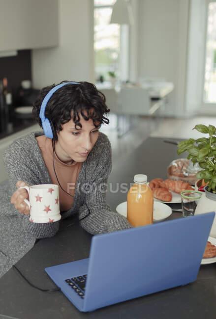 Жінка з навушниками працює з дому на ноутбуці на ранковій кухні. — стокове фото