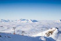 Télésiège et pentes ski pente avec montagnes opacifiés — Photo de stock