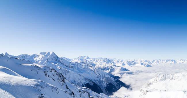 Catena montuosa innevata sopra le nuvole — Foto stock