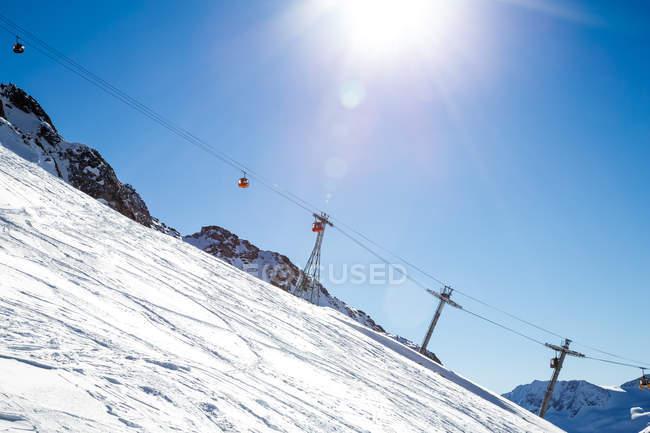 Vista diurna de cabines de estrada cabo sobre a encosta da montanha de neve — Fotografia de Stock