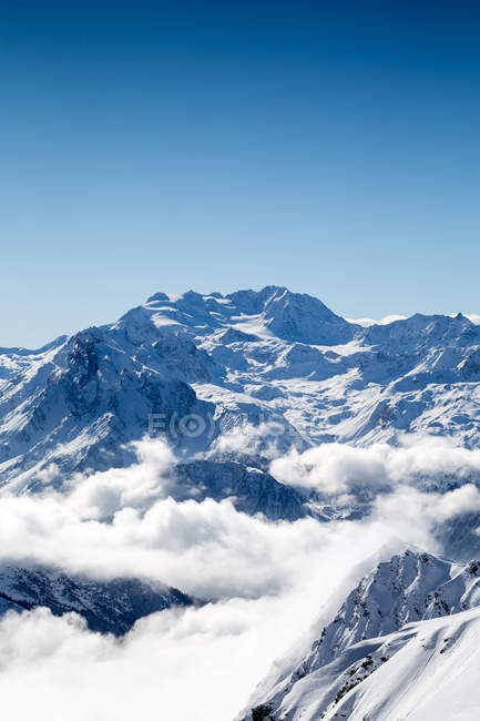 Snowy mountain peaks and glacier enshrouded in clouds — Stock Photo