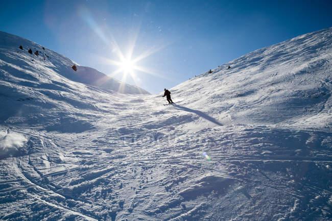 Vista de ângulo baixo de pessoa de esqui na encosta da montanha de neve — Fotografia de Stock
