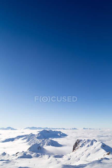 Chaîne de montagnes dans l'épaisse couche de nuages — Photo de stock