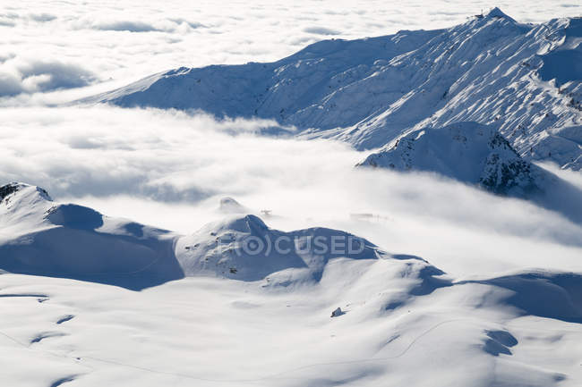Vue aérienne des montagnes couvertes de nuages et de la station de relevage station de ski dans la brume — Photo de stock