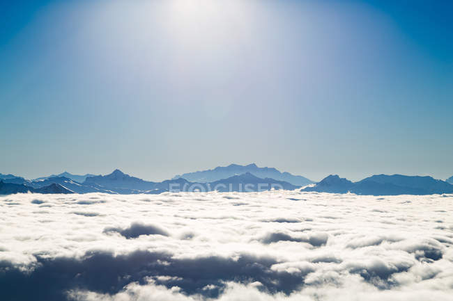 Mountain range in thick layer of clouds — Stock Photo
