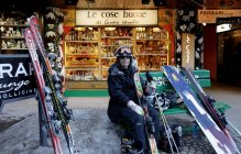 March 14, 2010. Italy, Madonna di Campiglio, Portrait of female skier sitting on bench with skiing equipment — Stock Photo