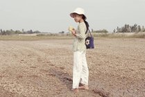 March 22, 2005. Vietnam. Portrait of girl with shoulder bag holding cup in field — Stock Photo