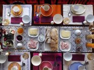 Top view of laid table with different dishes, drinks and settings — Stock Photo