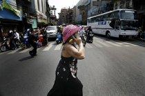 8 ноября 2006 года. Таиланд, Бангкок. Женщина переходит улицу и пользуется мобильным телефоном — стоковое фото