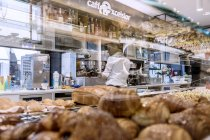 March 26, 2017. Italy, Trentino region, Trento. Person reflected in pastry stand in cafeteria — Stock Photo