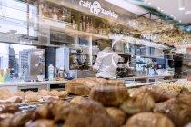 26 марта 2017. Италия, региона Трентино, Тренто. Лица, отражено в тесто стоять в кафетерии — стоковое фото
