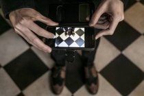 Cropped view of person photographing his shoes with smartphone — Stock Photo