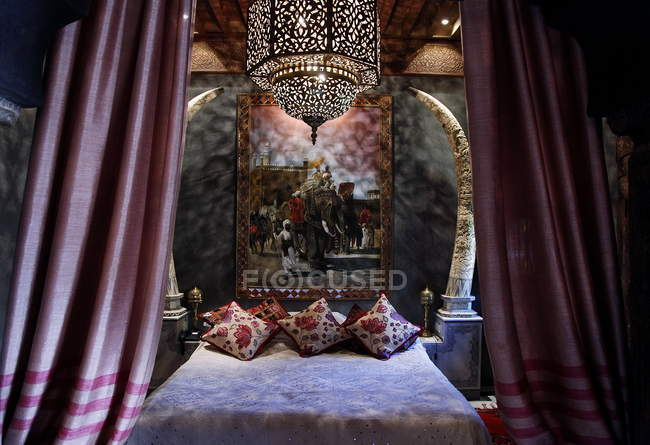 Morocco, Marrakesh, La sultana Marrakech hotel. Bed with pillows and painting — Stock Photo
