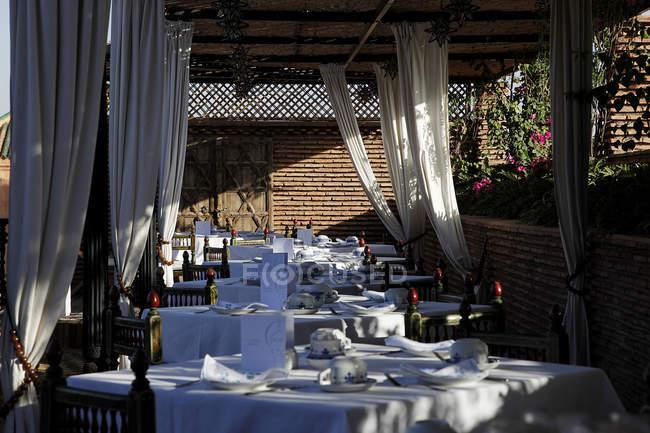 Marrocos, Marraquexe, La Sultana Marrakech hotel. Mesas colocadas em restaurante no terraço — Fotografia de Stock