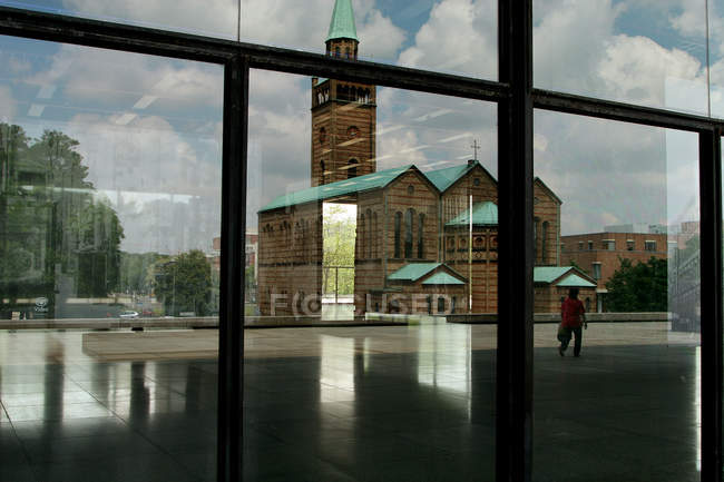 June 15, 2005. Berlin. Reflections in New National Gallery glass wall with church and walking person — Stock Photo