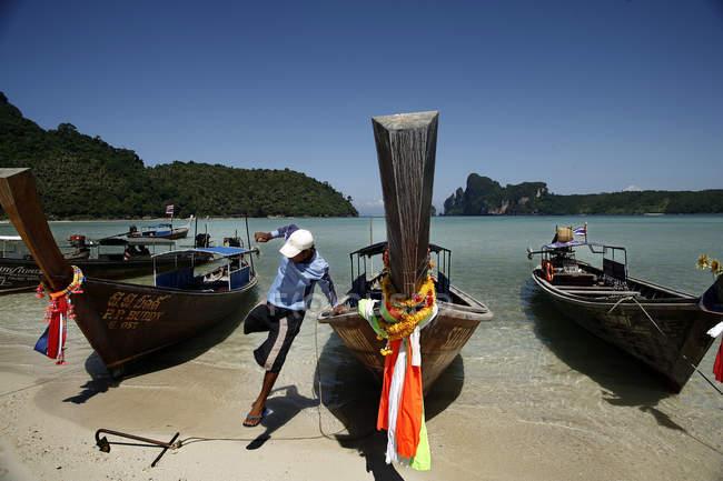 28 octobre 2006. La Thaïlande, l'île de Phi Phi, baie de Loh Dalum. Portrait d'un homme sautant du bateau sur le rivage sablonneux — Photo de stock