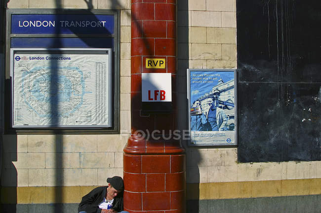 September 14, 2004. England, London, Camden district. Homeless man with can sitting by building wall — Stock Photo