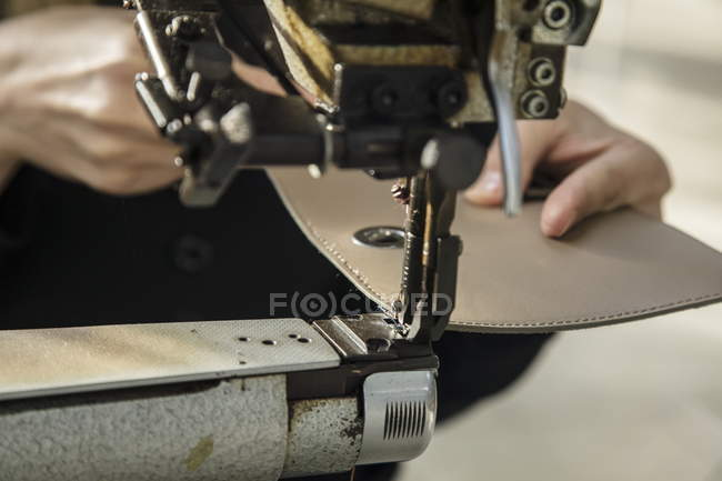 Closeup cropped view of hands holding leather piece in sawing machine — Stock Photo