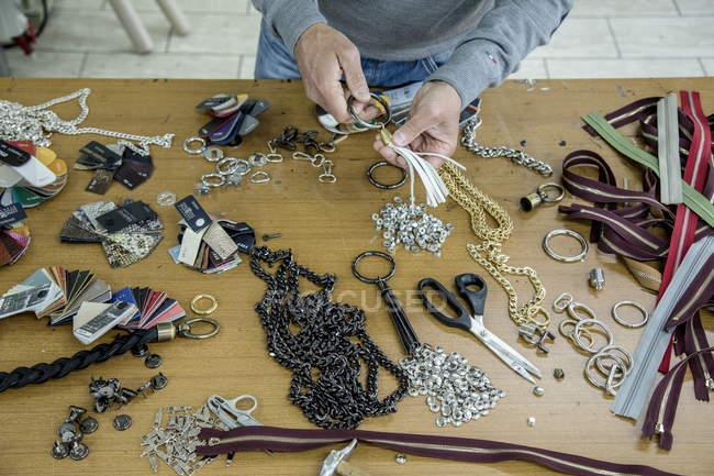 3 de noviembre de 2017. Italia, Tortoreto Lido. Vista recortada de la persona preparando accesorios metálicos para la producción - foto de stock