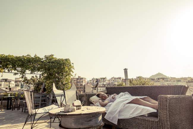 8 de agosto de 2017. Grécia, Atenas. Mulher dormindo no sofá terraço — Fotografia de Stock