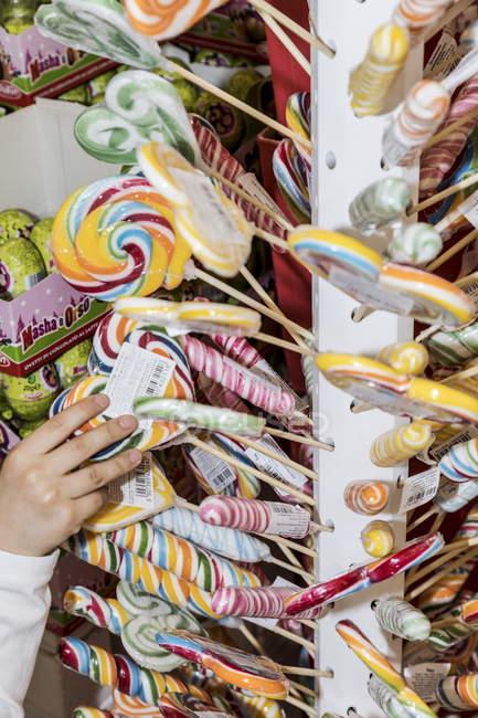 13. april 2017. italien, milan. Kinderhand greift in Süßwarenladen nach Süßigkeiten und Bonbons — Stockfoto