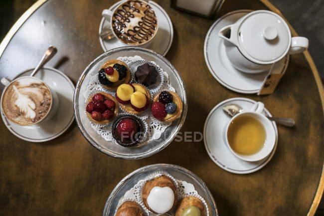 Вид зверху різні Фруктові торти з кави і чай на круглий стіл — стокове фото