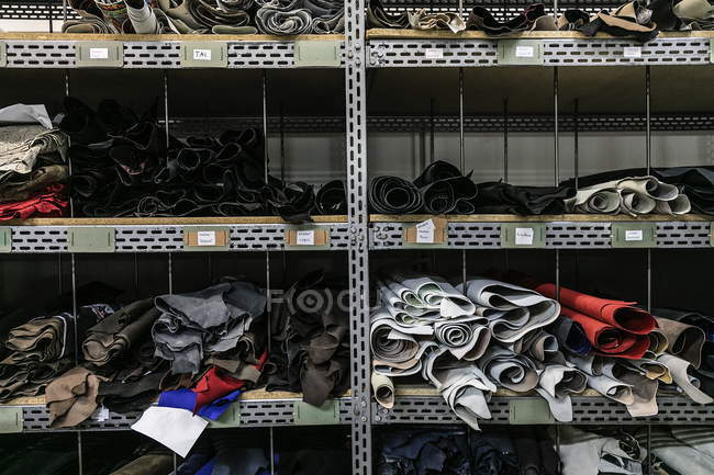 Colorful leather wraps and pieces on shelves of storage room — Stock Photo