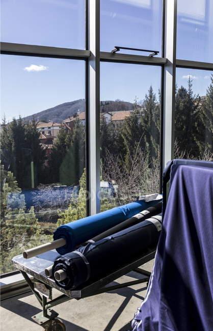 Bobinas de tela con las etiquetas en el carro junto a la ventana. Fábrica textil, Italia - foto de stock