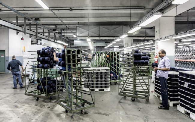1 марта 2017 года. Италия, Виссо, Бьелла, текстильная фабрика Реда 1865. Мужчины, работающие с пряжей и производственным оборудованием — стоковое фото