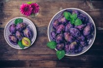 Фиолетовый Свежий урожай сливы в тарелках на деревянном столе, цветы в вазе, вид сверху — стоковое фото