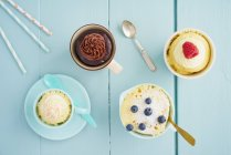 Top view of mug cakes in various cups on table — Stock Photo