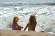 Two small girls sitting at sea waves — Stock Photo