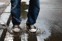 Vue partielle de la personne jambes sautant dans la flaque d'eau — Photo de stock
