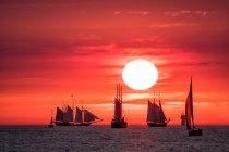 Cielo rosso di tramonto con barche a vela galleggianti in acqua di mare e sole — Foto stock