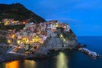 Mediterranean sea with illuminated Riomaggiore city houses on rocky hills — Stock Photo