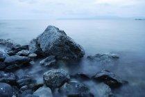 Côte de la mer avec des roches dans le brouillard — Photo de stock