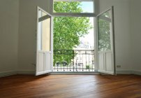 Janela aberta no quarto vazio, varanda e árvores verdes — Fotografia de Stock