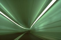 Blurred motion lights in tunnel with green neon lights — Stock Photo
