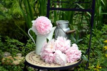 Garden chair with peony flowers, garden decoration — Stock Photo