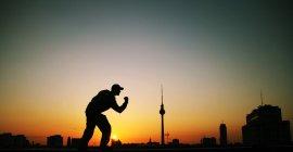 Sagoma di uomo che posa contro il tramonto con la Torre della televisione di Berlino — Foto stock